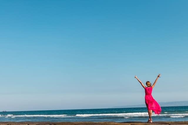 een vrouw in een rode jurk die aan de kust staat