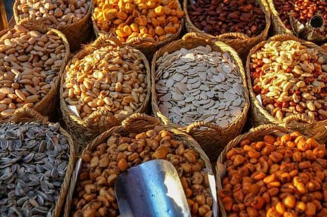 manden met verschillende soorten bonen en noten