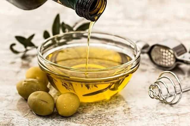 olie gegoten in een kom, groene olijven ernaast