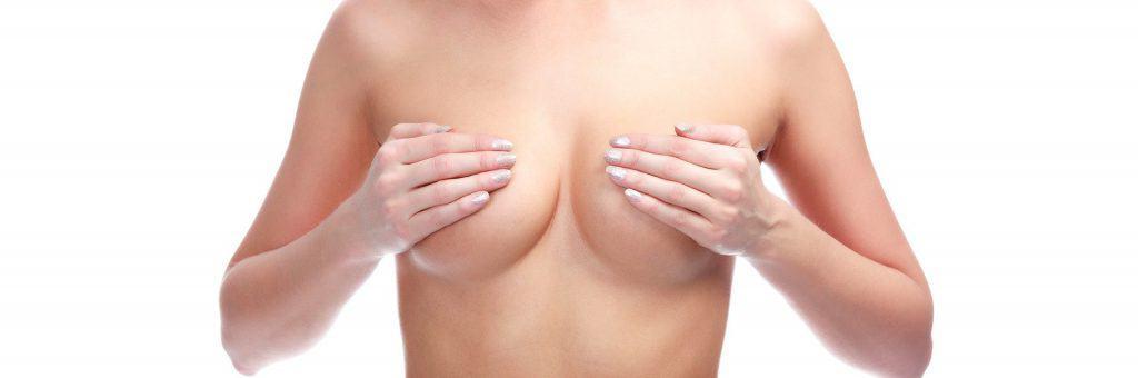 de vrouw bedekt haar borsten met haar handen