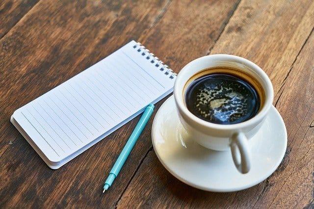 kopje koffie, blocnote, pen