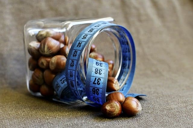 een potje noten verpakt in een maatje van een kleermaker