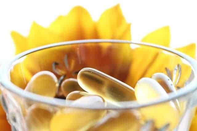 tabletten in een glas, gele bloem op de achtergrond