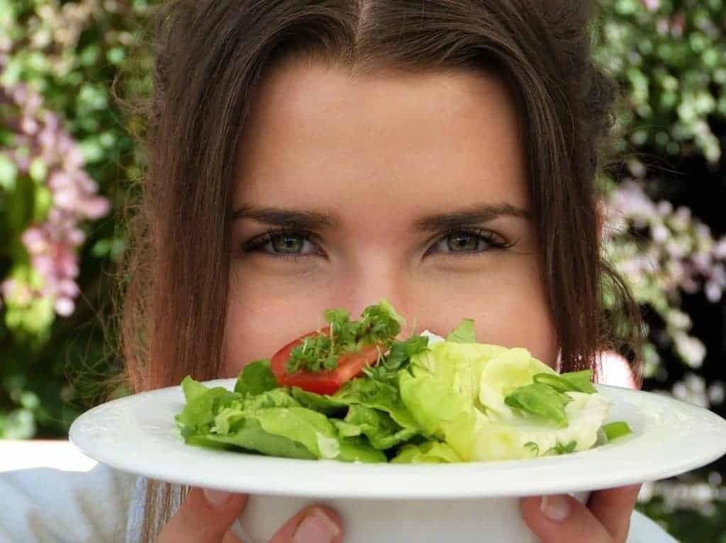 de vrouw houdt een bordje salade vast
