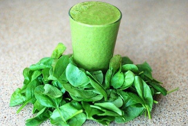 Een glas met een groene smoothie, spinazieblaadjes rondom
