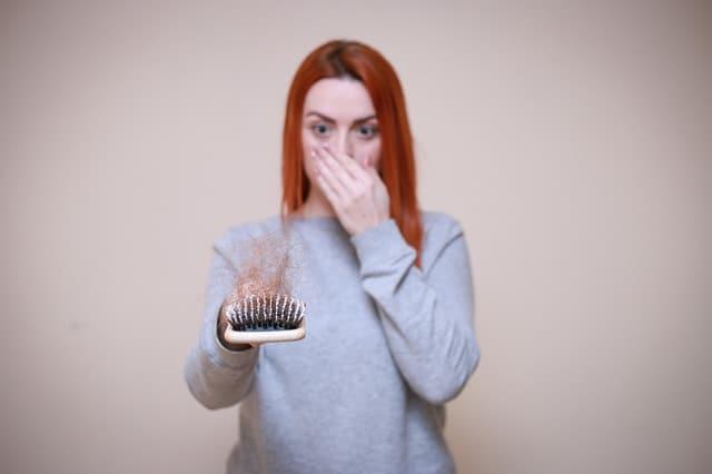een vrouw kijkt naar een haarborstel vol met haar