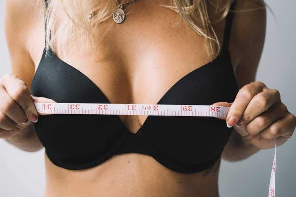 vrouw meet haar borsten met een centimeter