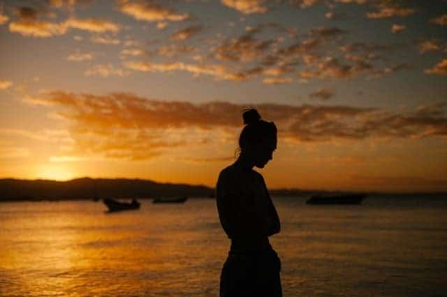verdrietige vrouw die op het strand loopt