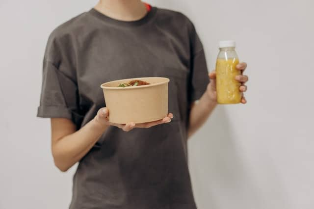 vrouw houdt een kom met voedsel en een shake vast