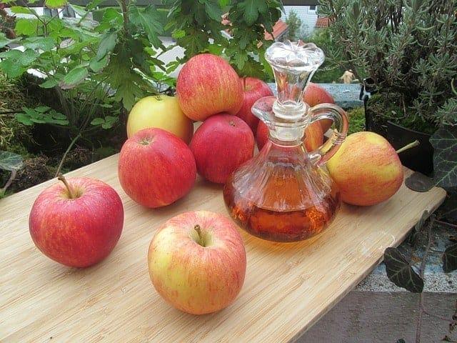 Verse appels en een fles appelciderazijn op de tafel