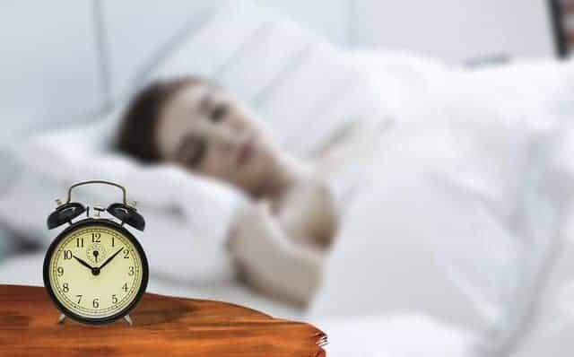 een vrouw slaapt met een wekker naast haar bed