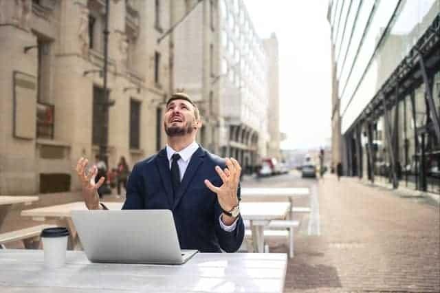 Een nerveuze man werkt op zijn laptop