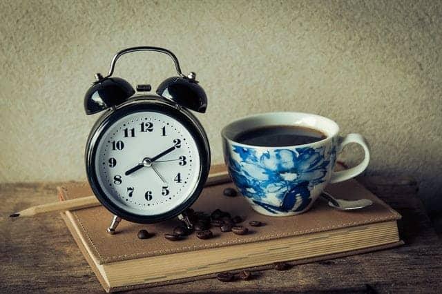 een kop koffie en een wekker