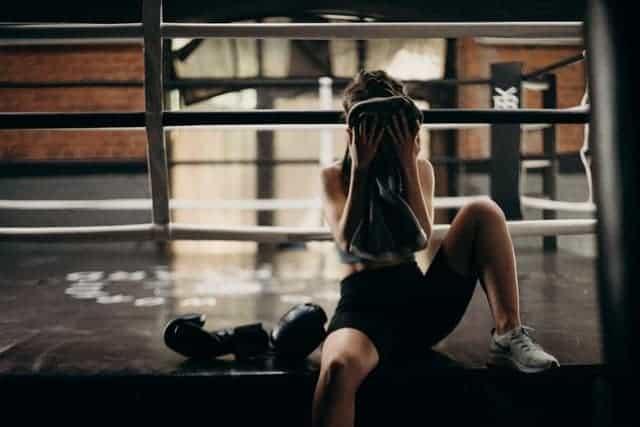 vrouw veegt zweet van haar gezicht na zware training
