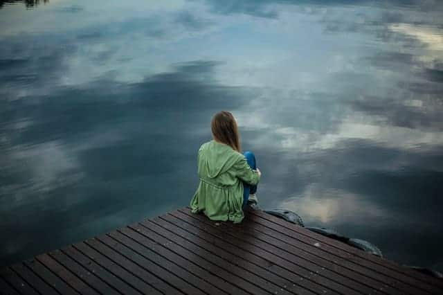 een vrouw zit op de rand van een pier en kijkt in het water