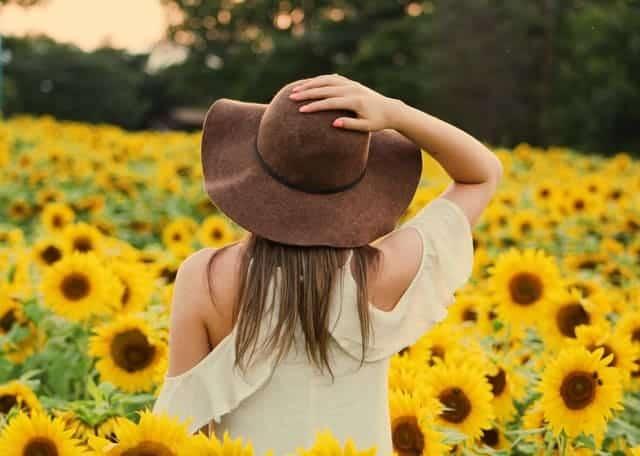 een vrouw loopt door een veld met zonnebloemen