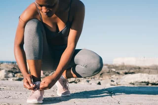 vrouw in sportkleding bindt haar schoen