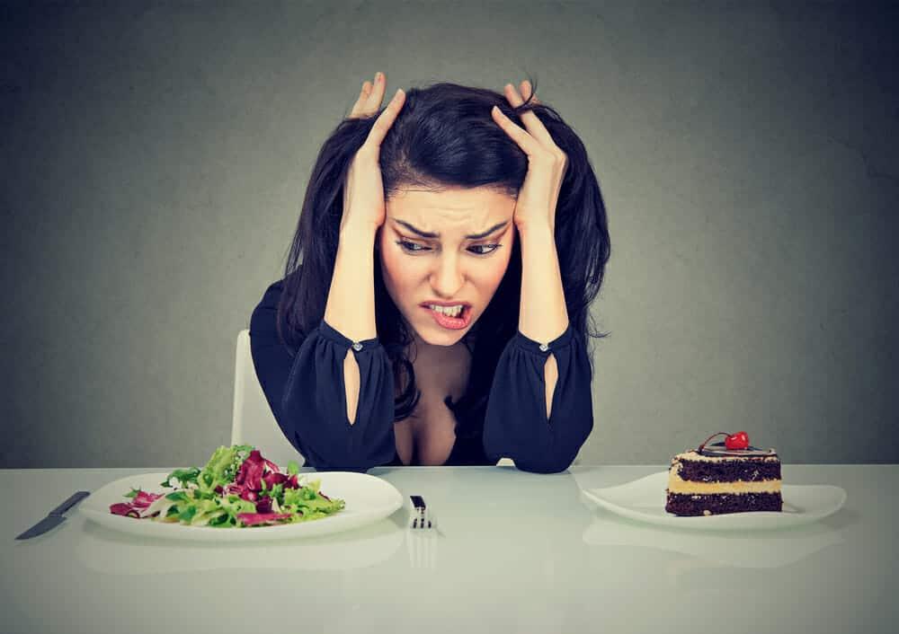 een vrouw zit aan een tafel met een bord cake en een bord salade