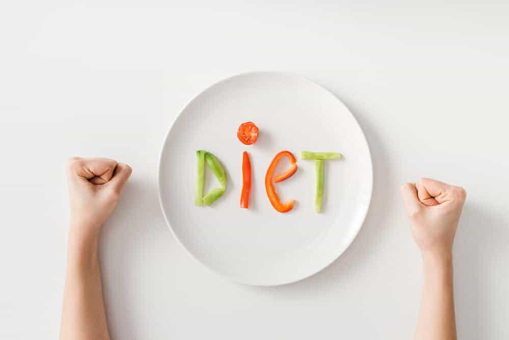 Gebalde vuisten, een bord, een paar stukjes groente op het bord