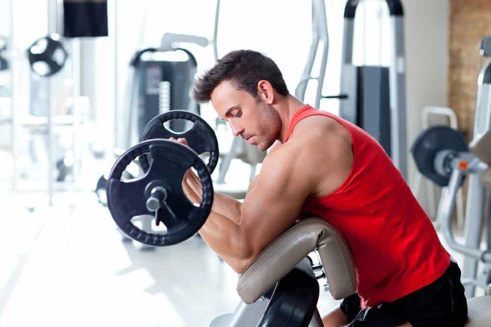 Een man oefent met een halter in de sportschool.